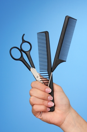 Color combs and scissors in female hand on color background photo