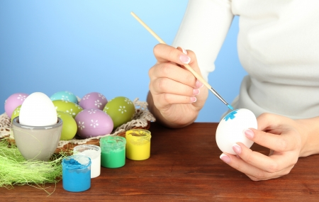Young woman painting Easter eggs, on color background photo