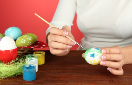 Young woman painting Easter eggs, on color background Stock Photo - 17760673