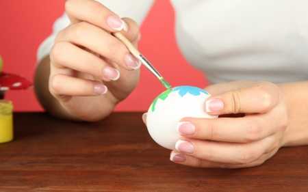 Young woman painting Easter eggs, on color background Stock Photo - 17760621