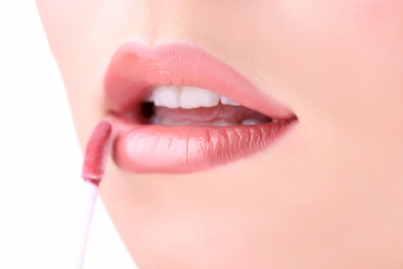 Beautiful young woman applying lip gloss, close up  photo
