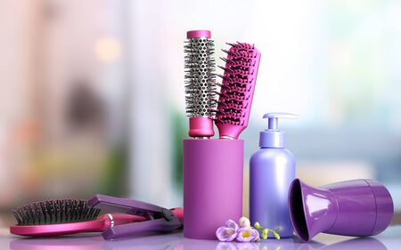 Hair brushes, hairdryer, straighteners and cosmetic bottle in beauty salon  Stock Photo - 17760606