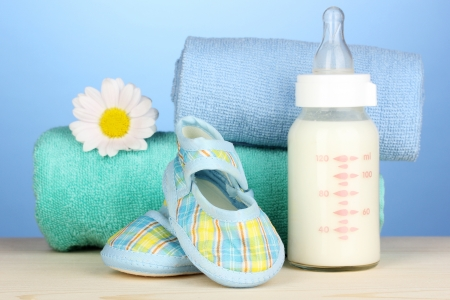 Baby bottle of milk with baby's bootees near towels on blue background Stock Photo - 17761010