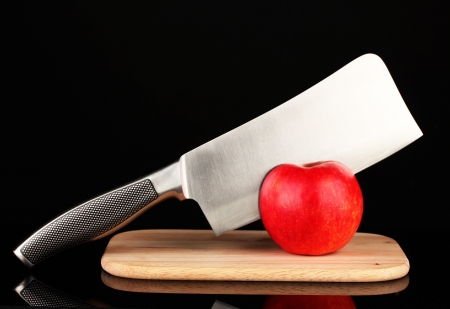 Red apple and knife on cutting board, isolated on black Stock Photo