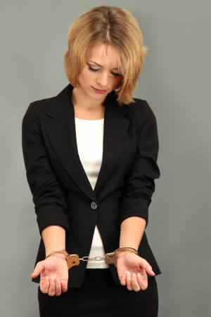 Young beautiful business woman in handcuffs on grey background Stock Photo