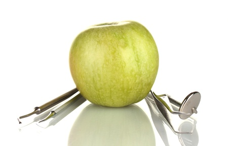 Green apple and dental tools isolated on white photo