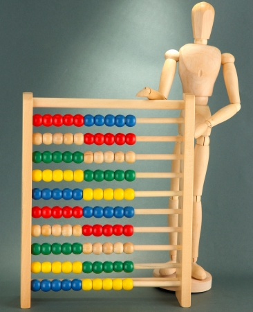 Bright toy abacus and wooden dummy, on grey background Stock Photo - 17770075
