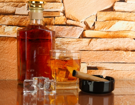 Bottle and Glass of whiskey and cigar on brick wall background photo