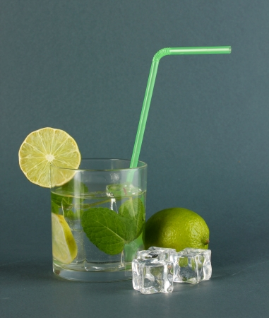 Glass of water with ice, mint and lime on grey background Stock Photo - 17770109