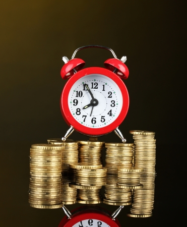 Alarm clock with coins on dark background photo