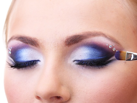 Beautiful female eyes with bright blue make-up and brush photo