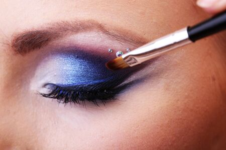 Beautiful female eye with bright blue make-up and brush photo