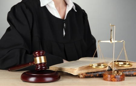 golden rule: Judge sitting at table during court hearings on grey background Stock Photo