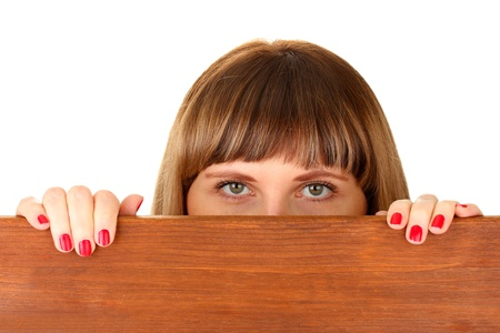 Woman peeking from wooden desk, isolated on white photo