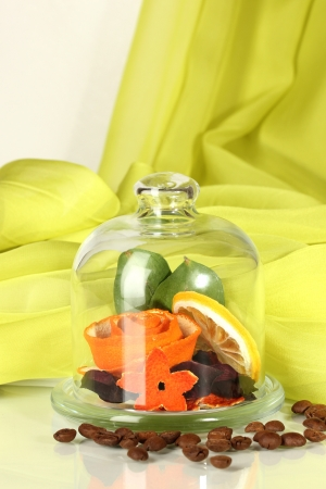 Decorative rose from dry orange peel in glass vase on white-green fabric background photo
