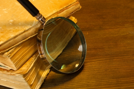 Magnifying glass and books on table Stock Photo - 17779087
