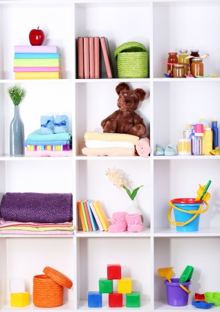 Beautiful white shelves with different baby related objects photo