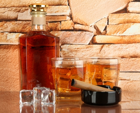 Bottle and Glasses of whiskey and cigar on brick wall background photo
