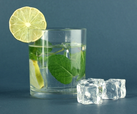 Glass of water with ice, mint and lime on grey background Stock Photo - 17778694
