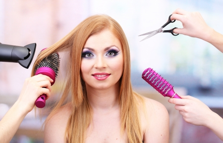 profesional: Beautiful woman and hands with brushes, scissors and hairdryer in beauty salon