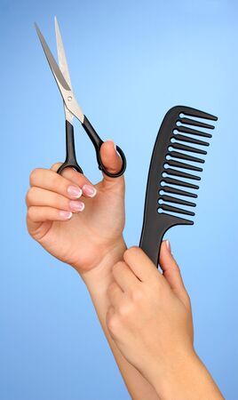 Color comb and scissors in female hand on color background photo