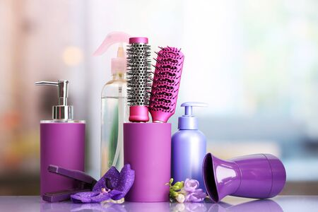 Hair brushes, hairdryer, straighteners and cosmetic bottles in beauty salon  photo