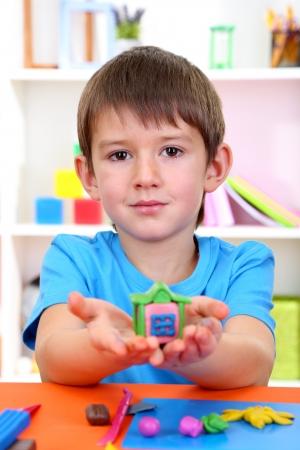 nurser: Cute little boy holding hand-made plasticine hourse over desk Stock Photo