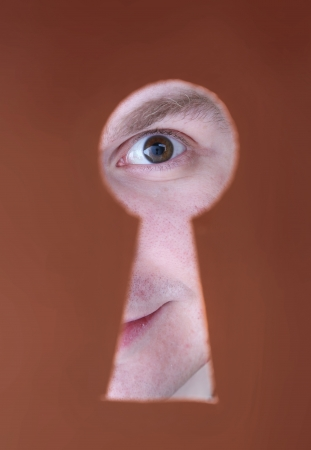 Man eye looking through hole in keyhole, on brown background photo