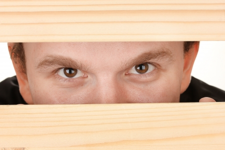 Man eyes looking through hole in wooden desk photo