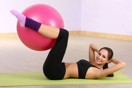 Young woman with gym ball at gymnasium photo