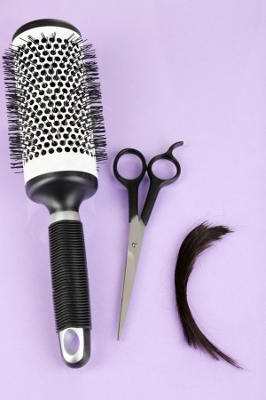 Pieces of hair cut with scissors on purple background photo