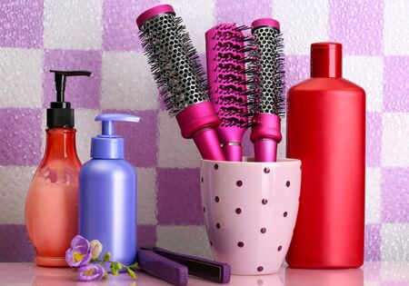 Hair brushes, hair straighteners and cosmetic bottles in bathroom  photo