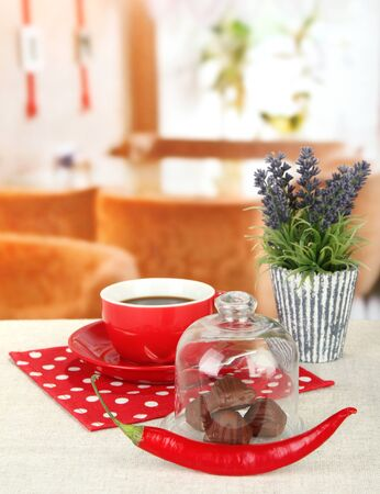 Chocolate sweets under glass cover and hot drink on bright background photo