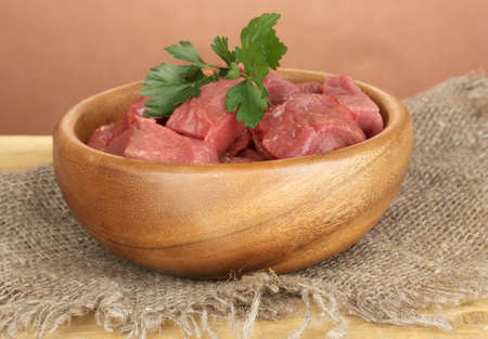 microelements: Raw beef meat in bowl on wooden table on brown background