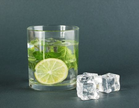 Glass of water with ice, mint and lime on grey background Stock Photo - 17866740
