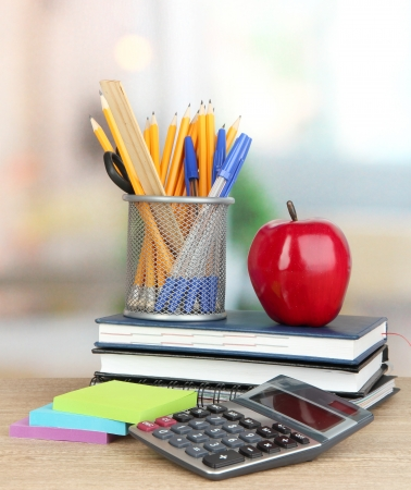 School supplies with red apple on wooden table photo