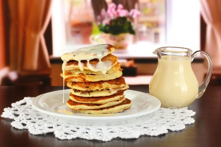 Sweet pancakes on plate with condensed milk on table in room Stock Photo - 17865987
