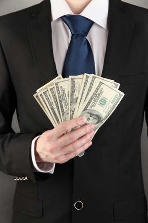 Business man holds lot of money on black background Stock Photo - 17866018