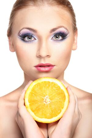 Beautiful young woman with glamour make up and orange, isolated on white photo