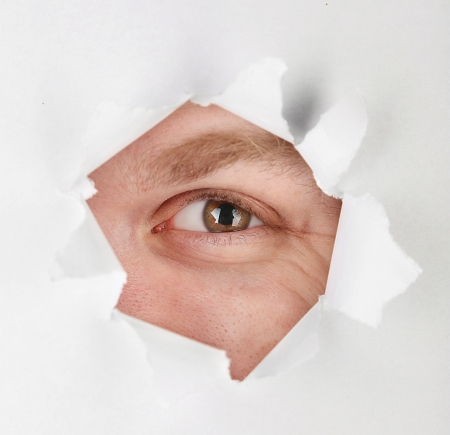Man eye looking through hole in sheet of paper photo