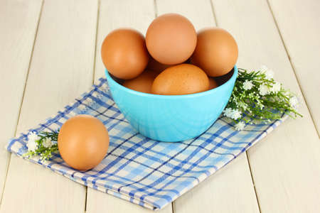 Eggs in blue bowl on wooden table close-up photo