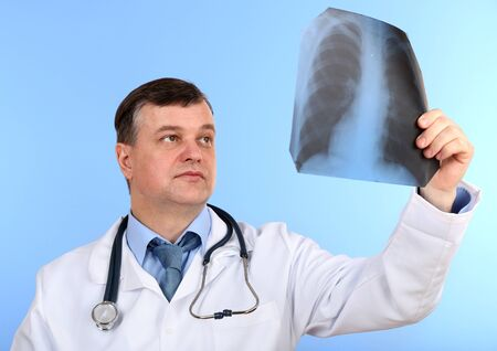 Medical doctor analysing x-ray image  on blue background Stock Photo - 21540142