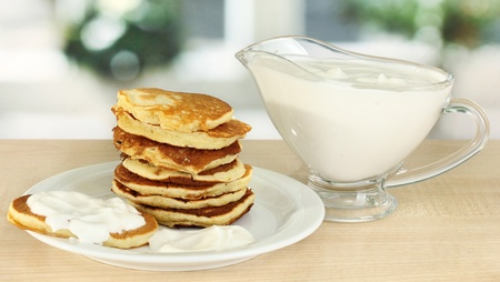 maslen: Sweet pancakes on plate with sour cream on table in kitchen