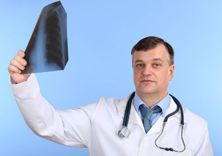 rentgen: Medical doctor analysing x-ray image  on blue background