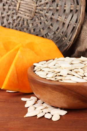 Pumpkin seeds in wooden bowl, on sackcloth background photo