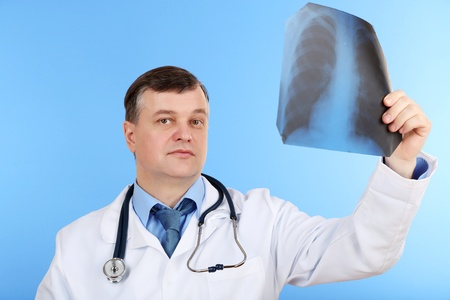 Medical doctor analysing x-ray image  on blue background Stock Photo - 21540650