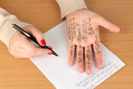 Write cheat sheet on hand on wooden table close-up Stock Photo - 17978951