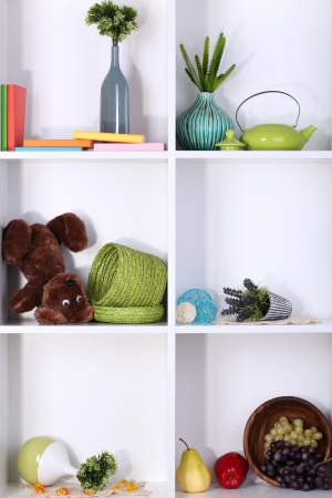 groups of objects: Beautiful white shelves with scattered different home related objects Stock Photo