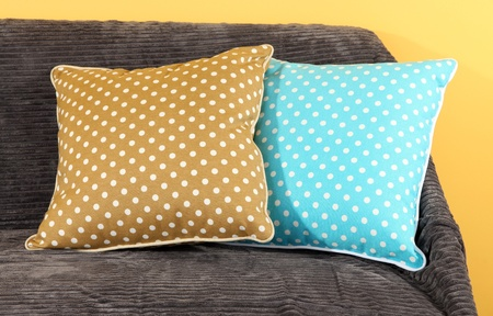 Colorful pillows on couch on yellow background Stock Photo - 18042274