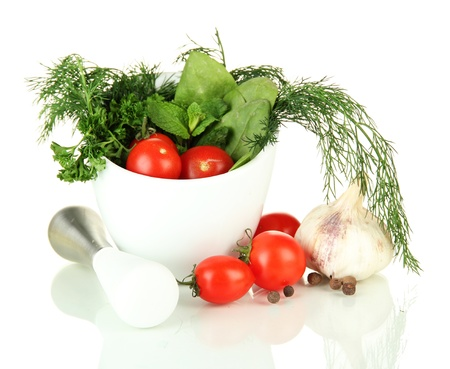 Composition of mortar, tomatoes and green herbals, isolated on white photo